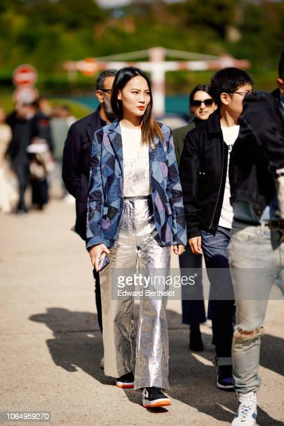 A guest wears a blue jacket a white top silver flare pants outside Dior during Paris Fashion Week Womenswear Spring/Summer 2019 on September 24 2018...