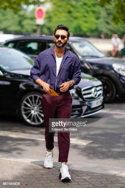A guest wears a blue jacket purple pants white sneakers outside Balmain during Paris Fashion Week Menswear SpringSummer 2019 on June 24 2018 in Paris...