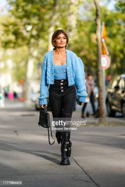 Guest wears a blue knit strapless top, a blue knit oversized jacket, black denim pants with bejeweled buttons, a black bag, black lace-up boots with...