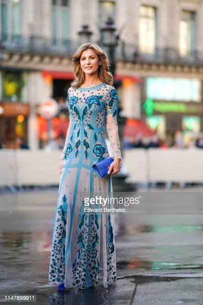 Guest wears a blue lace mesh floral print dress, a blue alligator skin bag, earrings, outside the Opera Garnier 350th Anniversary Gala in Paris on...