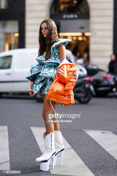 Guest wears a blue large ruffled dress with attached pillows, an orange puffer jacket, platform white boots with high heels, outside Balmain, during...