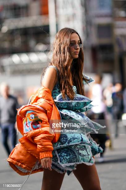 Guest wears a blue large ruffled dress with attached pillows, an orange puffer jacket, outside Balmain, during Paris Fashion Week - Womenswear Spring...