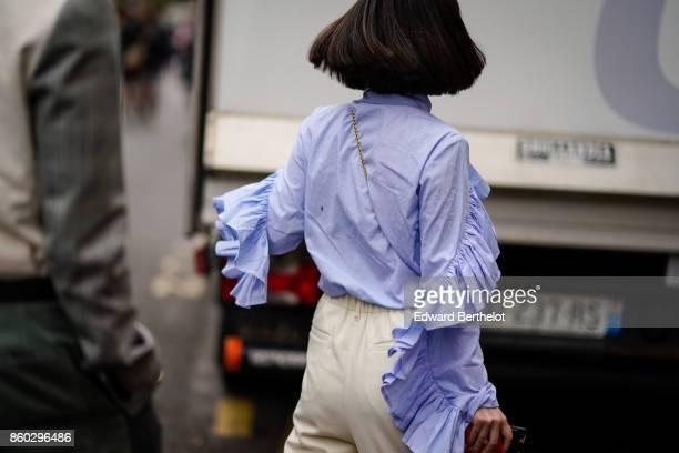 A guest wears a blue lavender flounced shirt outside Lanvin during Paris Fashion Week Womenswear Spring/Summer 2018 on September 27 2017 in Paris...