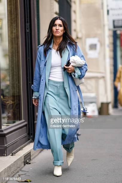 A guest wears a blue long jacket a white top light blue pants white shoes outside Thom Browne during Paris Fashion Week Womenswear Spring Summer 2020...