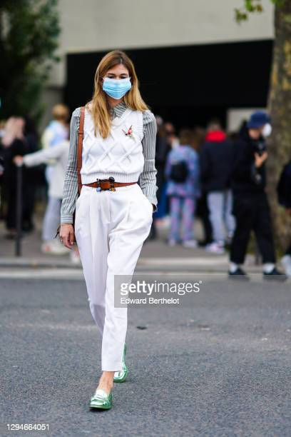 Guest wears a blue medical face mask, a white wool knitted sleeveless pullover, a gray striped shirt, a brown leather belt, white pants, green shiny...