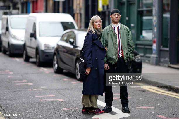 Guest wears a blue military jacket ; a guest wears a green bomber jacket, during London Fashion Week Men's January 2019 on January 05, 2019 in...