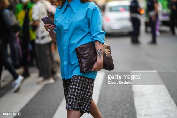 Guest wears a blue oversized shirt, black and white checkered large shorts, a brown shiny leather handbag, a white ring, outside the Max Mara fashion...