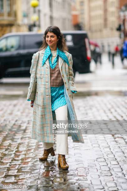 Guest wears a blue oversized silky OffDuty shirt, a checked brown vest, a tweed long coat, white pants, brown leather shoes, during London Fashion...