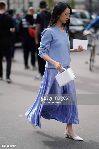 A guest wears a blue pleated skirt outside the Dries Van Noten show during Paris Fashion Week Womenswear Spring/Summer 2018 on September 27 2017 in...