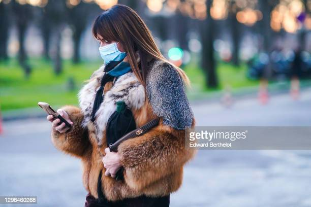Guest wears a blue protective face mask, a brown and gray fluffy faux fur winter coat, a Chanel bag, outside the Grand Palais, during Paris Fashion...