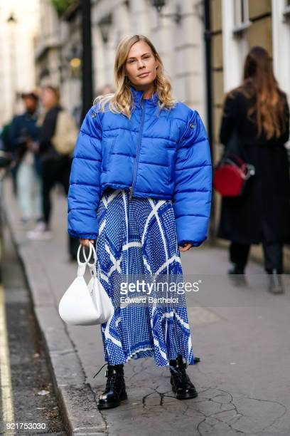 A guest wears a blue puffer coat with a blue skirt and a white bag during London Fashion Week February 2018 on February 16 2018 in London England