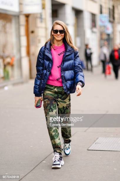 A guest wears a blue puffer jacket a pink top military camouflage print pants during Paris Fashion Week Womenswear Fall/Winter 2018/2019 on March 3...