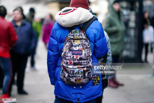 A guest wears a blue puffer jacket and a Jan Sport backpack during London Fashion Week Men's January 2018 at on January 6 2018 in London England