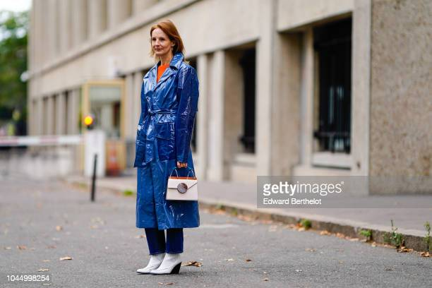 A guest wears a blue pvc trench coat a white bag white shoes outside Miu Miu during Paris Fashion Week Womenswear Spring/Summer 2019 on October 2...