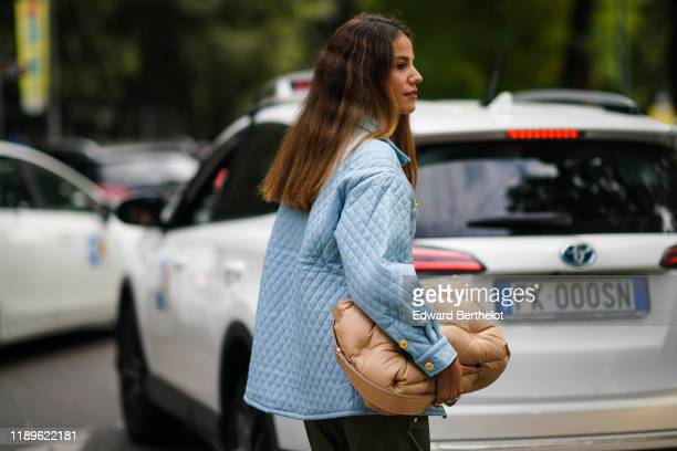 A guest wears a blue quilted jacket a camel puff bag outside the Fendi show during Milan Fashion Week Spring/Summer 2020 on September 19 2019 in...