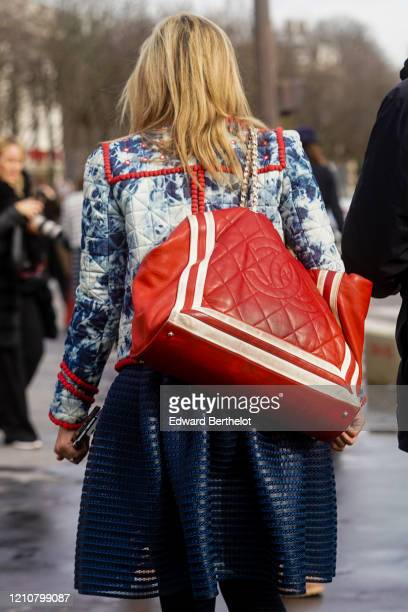 A guest wears a blue quilted jacket a red large quilted Chanel bag a mesh skirt outside Chanel during Paris Fashion Week Womenswear Fall/Winter...
