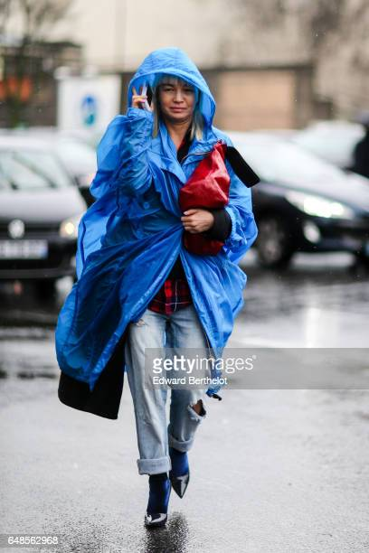A guest wears a blue raincoat and a red leather bag outside the Celine show during Paris Fashion Week Womenswear Fall/Winter 2017/2018 on March 5...