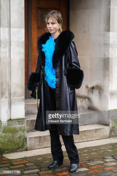 A guest wears a blue ruffled top a black leather long coat with fluffy parts black pants black leather pointy shoes during London Fashion Week Fall...