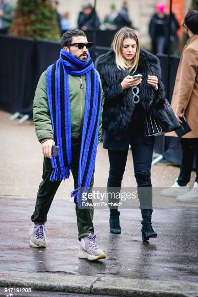 A guest wears a blue scarf sunglasses a green bomber jacket sneakers a guest wears a black fur coat high boots outside Dior during Paris Fashion Week...