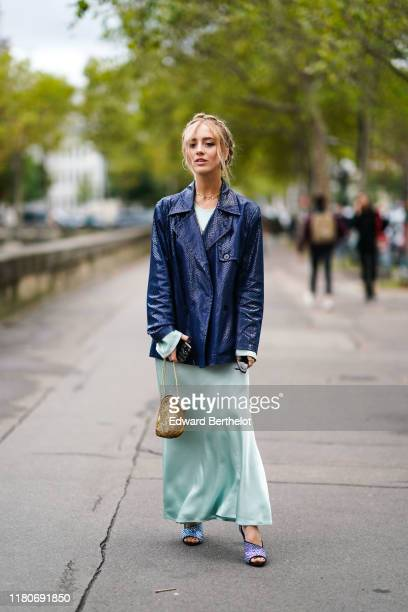 Guest wears a blue shiny crocodile pattern jacket, a pale green lustrous flowing dress, a bag, outside Valentino, during Paris Fashion Week -...