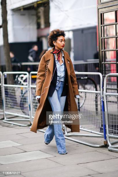 A guest wears a blue shirt a fawn color coat blue flare jeans during London Fashion Week February 2019 on February 19 2019 in London England