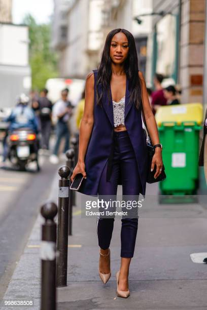 A guest wears a blue sleeveless jacket blue pants nude colored shoes a cropped top outside Thom Browne during Paris Fashion Week Menswear...
