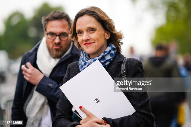 A guest wears a blue speckled scarf a black jacket outside the Chanel Cruise Collection 2020 At Grand Palais on May 03 2019 in Paris France