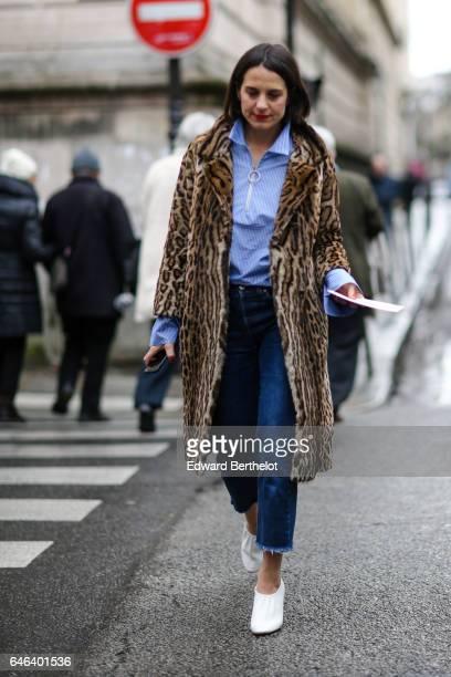 A guest wears a blue striped shirt a leopard print fur coat blue denim jeans pants and white shoes outside the JOUR/NE show during Paris Fashion Week...