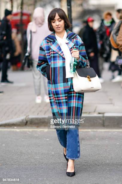 A guest wears a blue tartan coat blue jeans a black and white bag during London Fashion Week Men's January 2018 at on January 6 2018 in London England