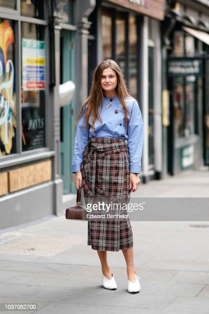 A guest wears a blue top a tartan checked skirt white shoes during London Fashion Week September 2018 on September 14 2018 in London England