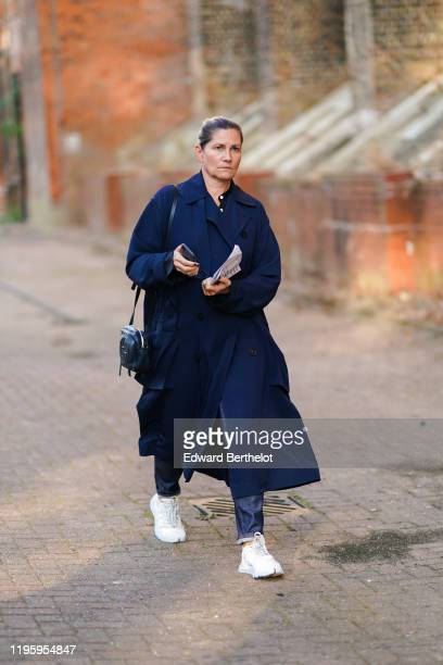 Guest wears a blue trench coat, a black bag, white sneakers, during London Fashion Week September 2019 on September 15, 2019 in London, England.