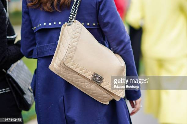 A guest wears a blue trench coat with a studded back flap a cream color Chanel bag outside the Chanel Cruise Collection 2020 At Grand Palais on May...