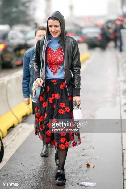 A guest wears a blue tshirt with a printed red heart a black leather perfecto jacket a hood a balck mesh pleated skirt with red printed flowers black...