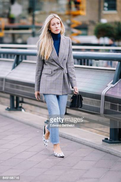 A guest wears a blue turtleneck a gray blazer jacket blue cropped jeans shoes outside Versus during London Fashion Week September 2017 on September...