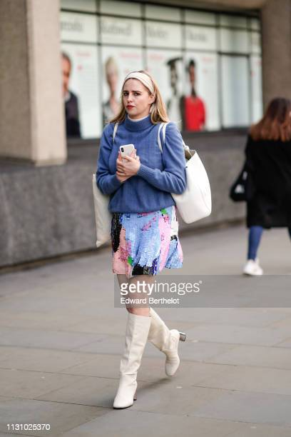A guest wears a blue turtleneck a shiny colorfully sequined skirt a black bag beige kneehigh boots during London Fashion Week February 2019 on...