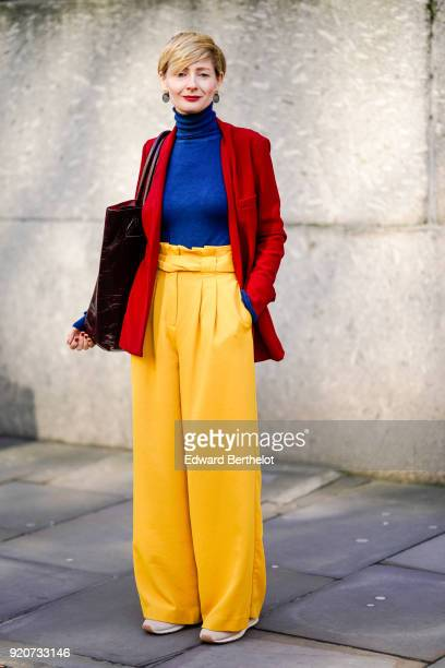 A guest wears a blue turtleneck pull over a red jacket yellow pants during London Fashion Week February 2018 on February 17 2018 in London England