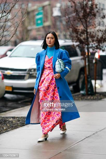Guest wears a blue turtleneck pullover, a blue long coat with puff sleeves, a pale blue Bottega Veneta quilted bag, a pink and purple floral print...