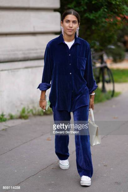 A guest wears a blue velvet outfit white sneakers a white bag outside Issey Miyake during Paris Fashion Week Womenswear Spring/Summer 2018 on...