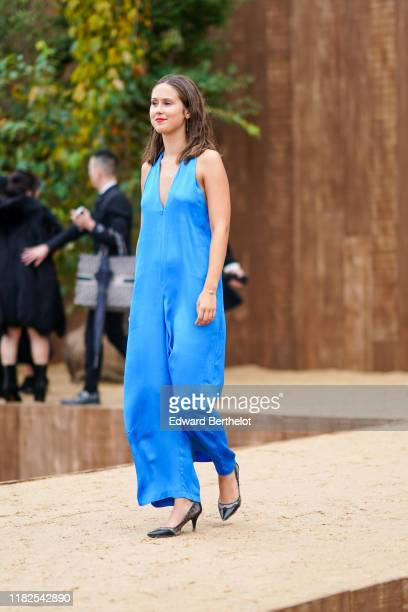 Guest wears a blue v-neck jumpsuit, outside Dior during Paris Fashion Week - Womenswear Spring Summer 2020, on September 24, 2019 in Paris, France.