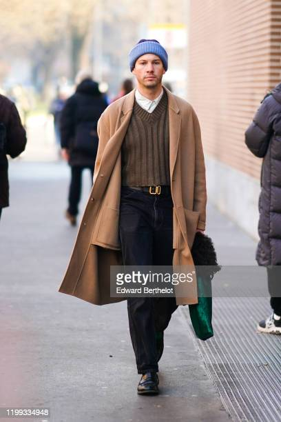 Guest wears a blue wool beanie hat, a light brown long coat, a brown wool v-neck pullover, a white shirt, a belt, black pants, leather shoes, outside...