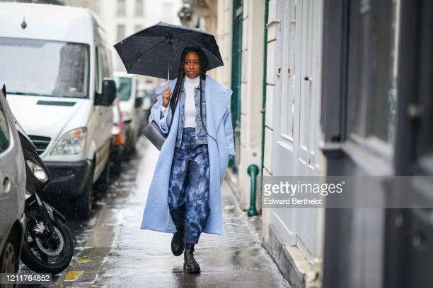 A guest wears a blue wool coat a white turtleneck pullover a blue denim jacket blue pants black leather shoes a bag during Paris Fashion Week...