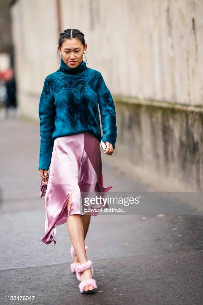 Guest wears a blue wool turtleneck pullover, a pink silky skirt, pink fluffy shoes, earrings, a pink bag, outside Valentino, during Paris Fashion...