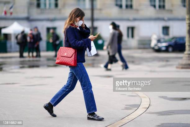 Guest wears a blue woven jacket with fringes, a red leather padded bag from Chanel, blue jeans, black socks, black leather shiny Chanel shoes,...