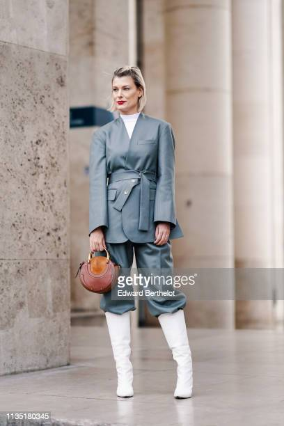 A guest wears a blue wrapover jacket a white top blue pants black boots a brown Chloé round bag outside Atlein during Paris Fashion Week Womenswear...