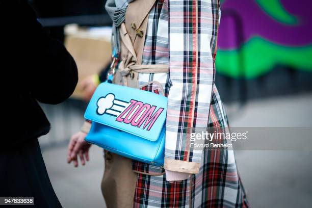 A guest wears a blue 'ZOOM' bag a tartan jacket during London Fashion Week Men's January 2018 at on January 6 2018 in London England