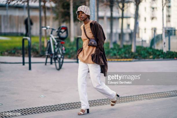 A guest wears a bob checked Burberry hat a brown jacket a brown top a leather bag white pants shoes outside Chloe during Paris Fashion Week...