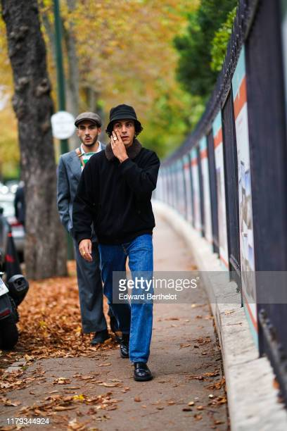 Guest wears a bob hat, a black jacket with fluffy brown collar, blue jeans, black leather shoes, a ring, outside Lacoste, during Paris Fashion Week -...