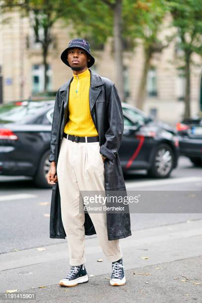 Guest wears a bob hat, a black leather trench long coat, a yellow pullover, a necklace, a belt, white pants, Converse sneakers shoes, outside Paco...