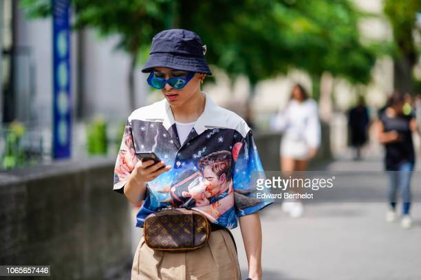 A guest wears a bob hat a shirt with printed image depicting a man and a woman kissing a belt bag from Louis Vuitton outside Rick Owens during Paris...