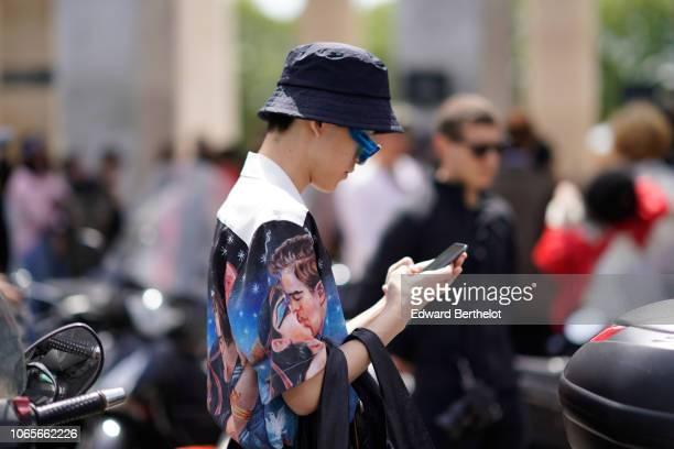 A guest wears a bob hat blue sunglasses a shirt outside Rick Owens during Paris Fashion Week Menswear SpringSummer 2019 on June 21 2018 in Paris...